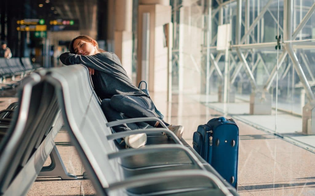 Nainen nukkuu matkalaukun kanssa lentokentällä
